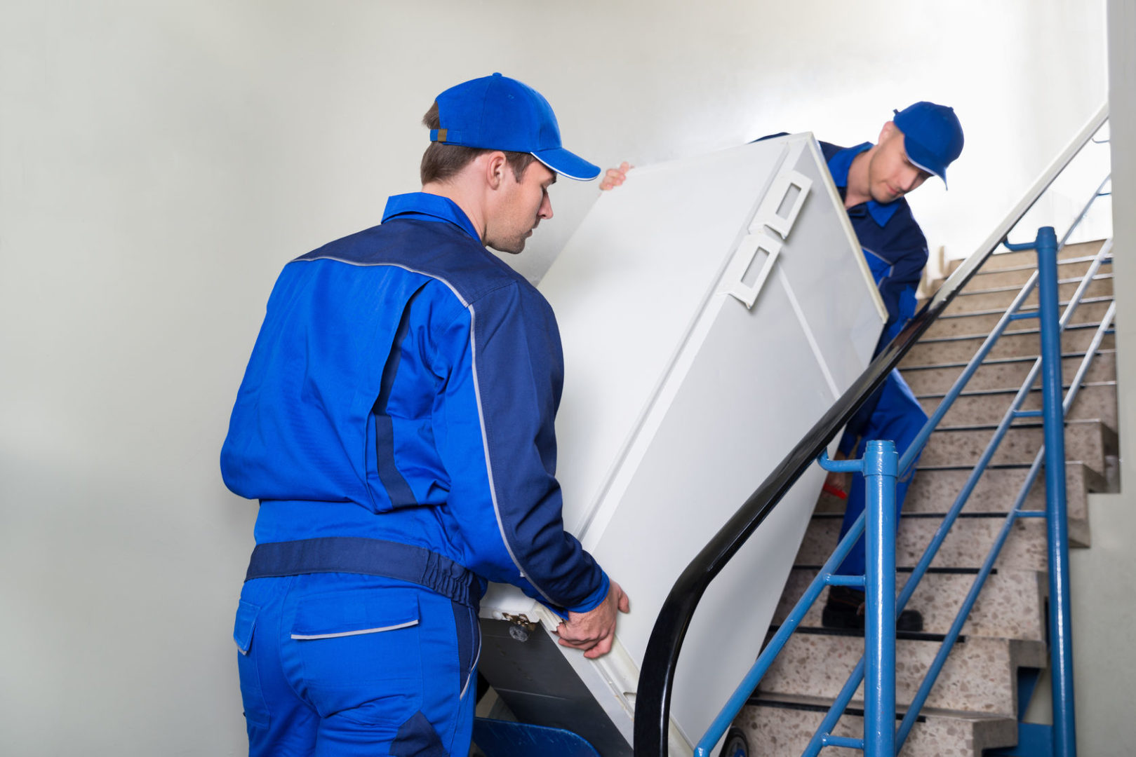 51450773 - young male movers carrying refrigerator while climbing steps at home